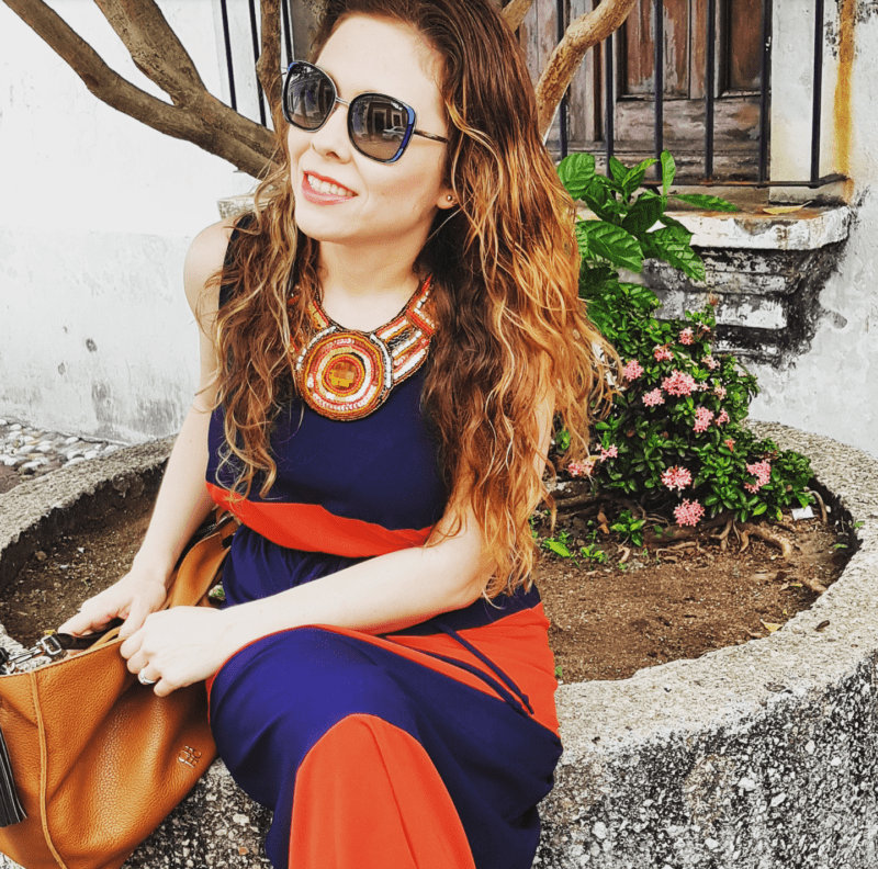 Maxidress a rayas colores azul y naranja. Bolso en color camel Carolina Herrera
