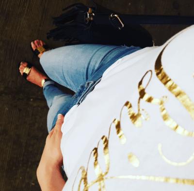 Outfit Blusa slogan Bride en blanco, pantalones de mezclilla Old Navy y sandalias negras con dorado de pulsera Tory Burch