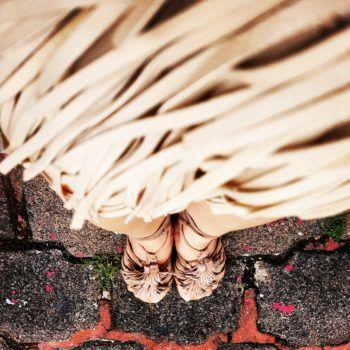 Fotografia toma desde arriba bolso de flecos en color beige, sandalias con flecos Steve Madden
