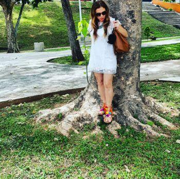 Outfit completo, túnica en encaje blanco, sandalias con pompones de colores y Bolso Camel de Carolina Herrera